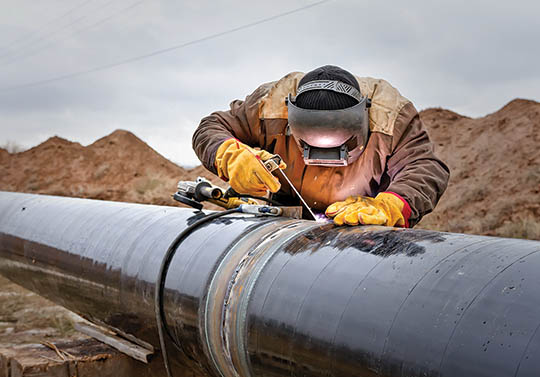 worker welding gas pipeline